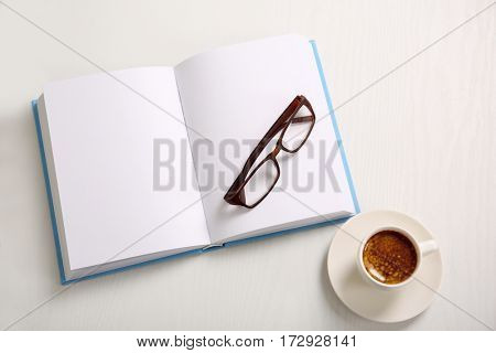 Open book with cup of coffee, on white wooden table