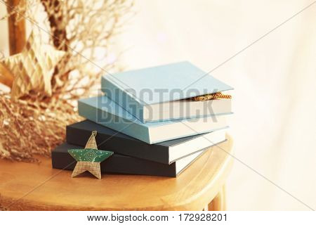 Pile of books and decor on wooden chair, closeup