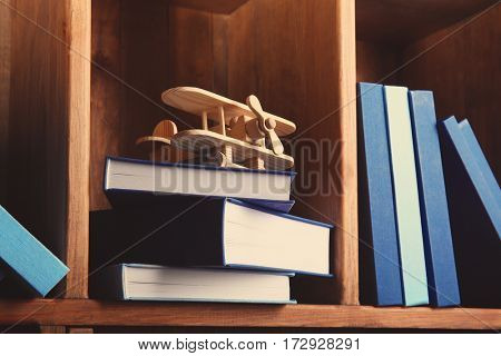 Stack of books with airplane on wooden shelf