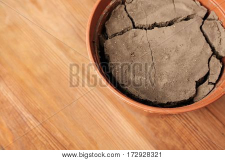 Water shortage concept. Pot with dry soil on wooden background