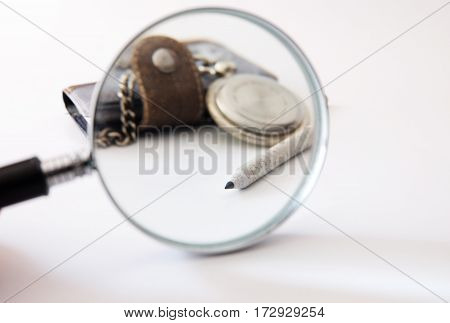 through magnifier old clock notebook pencil isolated