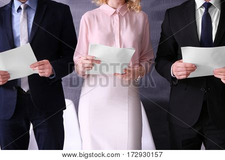 Group of people with paper in hands waiting for interview indoors