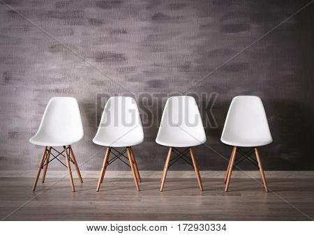 Four white chairs in office corridor