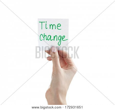 Female hand holding note with phrase TIME CHANGE on white background