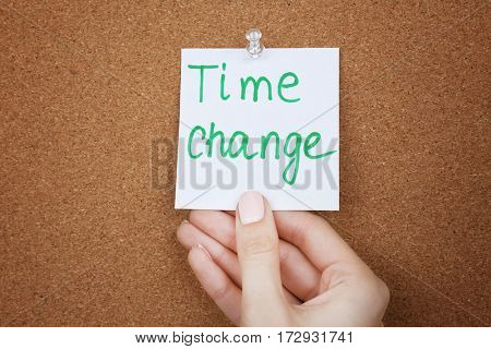 Female hand holding note with phrase TIME CHANGE on cork board background