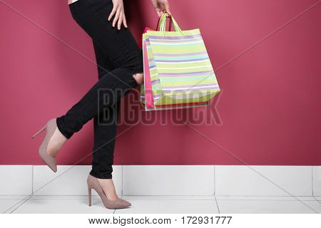 Legs of beautiful young woman with paper bags indoors