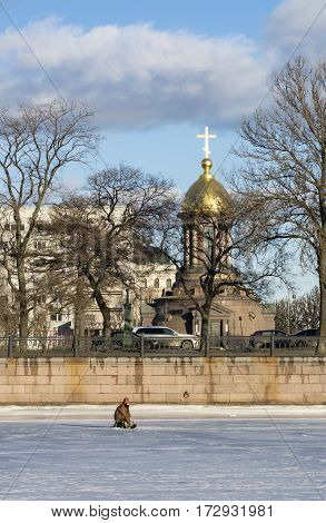 Shrine chapel of the Holy Trinity in St. Petersburg embankment Kamennoostrovsky Prospekt a fisherman on the ice of the Neva river fishing winter snow Sunny day
