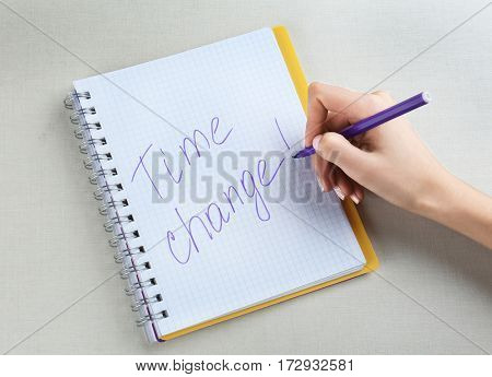Female hand writing phrase TIME CHANGE in notebook