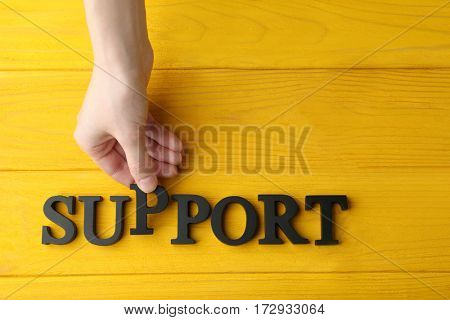 Female hand and word SUPPORT on wooden background
