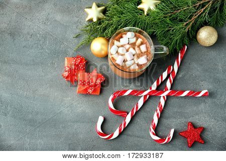 Christmas composition with candy canes, cup of coffee and decorations on grey table