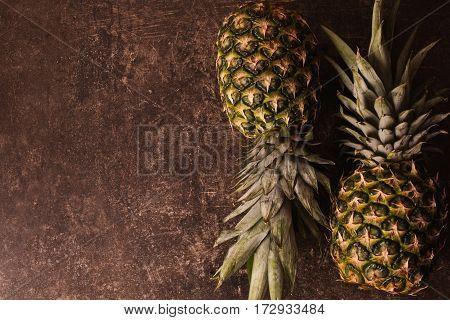 Two ripe pineapple lying on a dark marble table. Delicious fruit. Healthy eating. Pineapple on the table