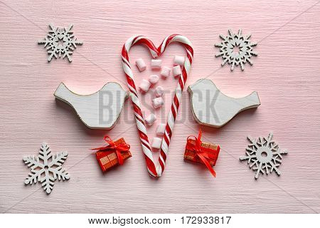 Christmas composition with candy canes and decorations on wooden background