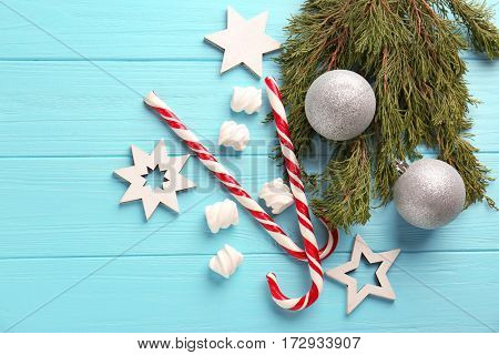 Christmas decoration with candy canes on blue wooden background
