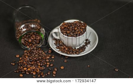 top view on an aromatic coffee beans in a white cup and spilled coffee beans from an overturned jar artistic decoration