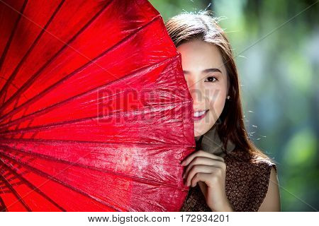 Laos girls has a red umbrella beautiful woman fronting her half.