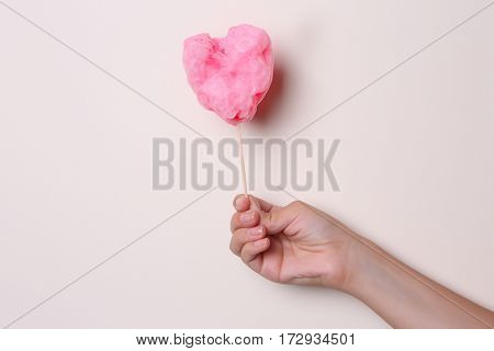 Female hand holding sweet cotton candy on light background