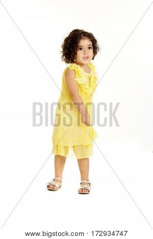 little girl in a yellow dress posing on a white background