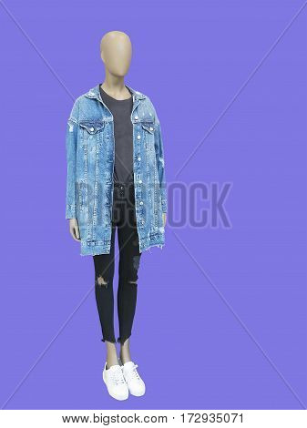 Full-length female mannequin dressed in jeans jacket and ripped leggings isolated.