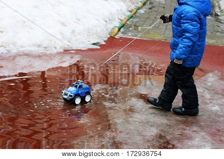 The snow is melting. The image of a child dressed in a jacket boots gloves. A child plays on the Playground with toy car: the car driven through a puddle on the rope.