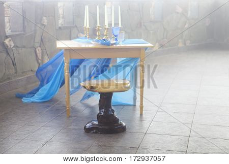 Table setting in vintage style is decorated with candles in golden and blue colors