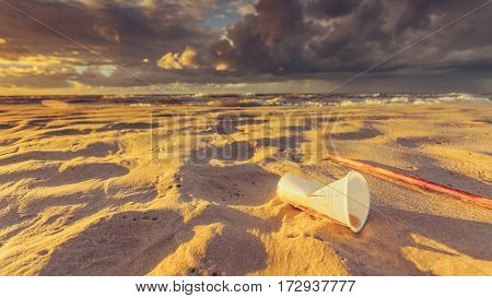 Plastic Disposable Cup On Sea Shore. Earth Ecology