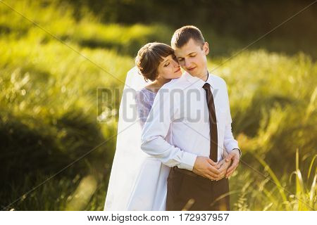 Groom and bride in a white wedding dress on a background of nature. Wedding photography. Happy family. Wedding couple. Wedding concept