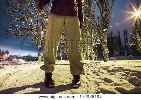 Human feet standing snowy road night street lamps