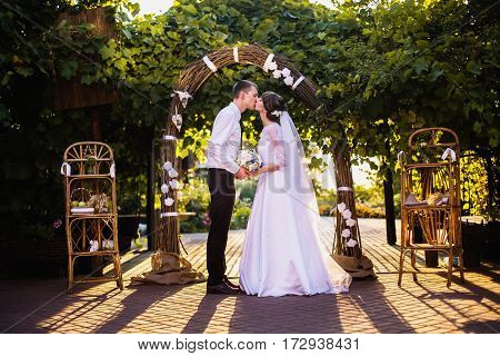Kiss of groom and bride in a white wedding dress on a background of a wedding arch of willow branches. Wedding photography. Strong kiss