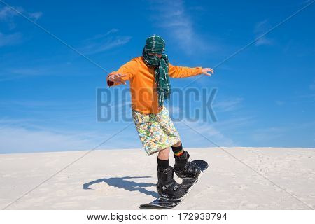 Man Wearing A Scarf Engaged In Snowboarding In Desert