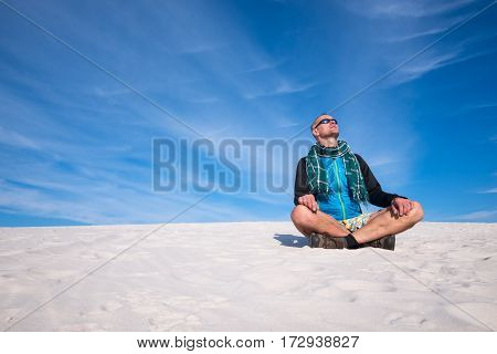 Traveler dreaming and relax among sand dunes on the background of colorful sky. Wonderful travel in the desert.