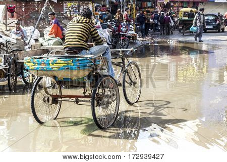 Young Rickshaw Driver Waits For Guests At The Flooded Street In Rainy Season