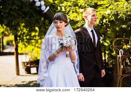 Groom and bride in white wedding dress on background of the arch. Wedding ceremony. Happy family