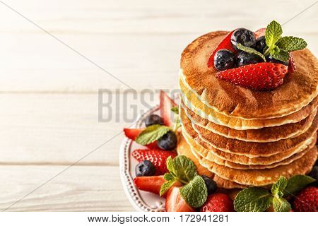 Homemade pancakes with berries and fruit on a white background, selective focus.