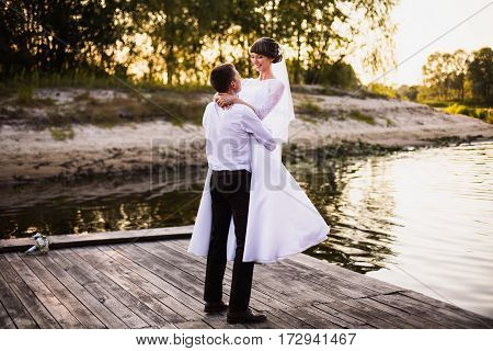 Happy groom and bride in white wedding dress on background of water. Wedding photography. A happy family