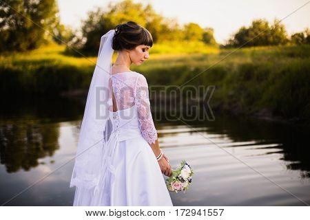The bride in a white wedding dress on nature background. Wedding photography. Bride in wedding gown