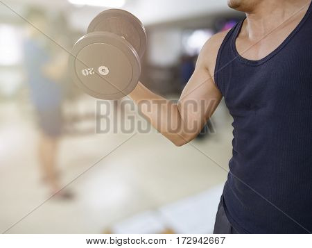 Man training in the gym - dumbbell biceps curl