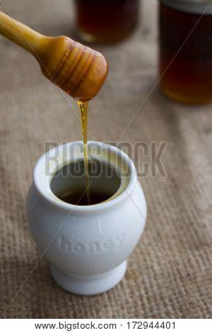 Honey dripper over a white honey pot.
