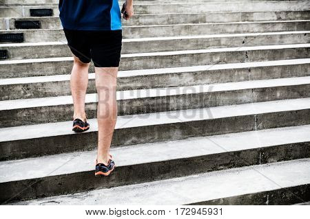 Man runner running on concrete stairs in city. Young male athlete training and doing workout outdoors in city. Endurance training fitness and exercising outdoors in urban environment.