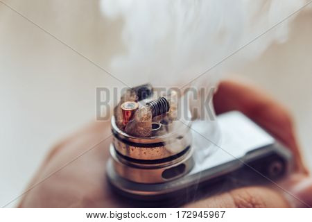 Man's hand holding Mod for vaping, vape device and dripping RDA without top cap, coils. Electronic e - cigarette,  vaporizer, vape, for quit smoke e-liquid.