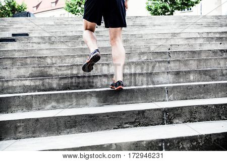 Man runner running on stairs in city. Young male athlete training and doing workout outdoors in city. Fitness training and exercising outdoors in urban environment.