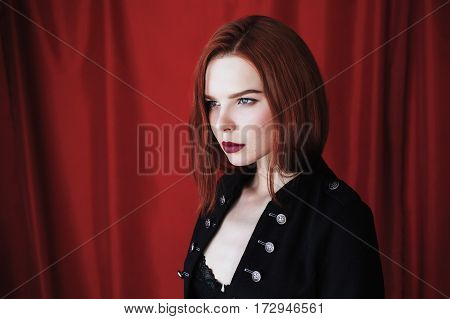 Beautiful redhead woman with parted lips in black lingerie on red background looking away. Fashion photography. Bright appearance. Red hair woman. Portrait in profile of redhead model