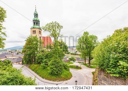 View of old catholic church in salzburg, green and red roof, winding road and trees, rainy day, austria