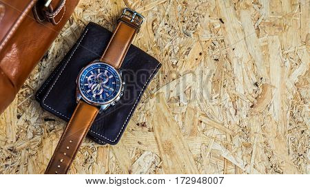 Men's fashion with  brown leather bag, watch, wallet on wooden floor.