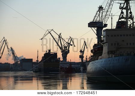 seaport silhouettes of ships and portal cranes in evening sky