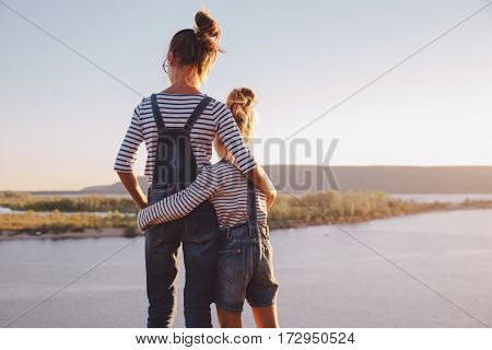 sisters hugging while looking at nature