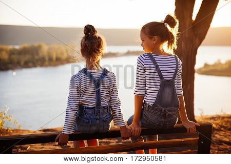 a warm summer evening, two little girls are watching the sunset