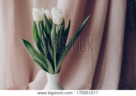 Stylish White Tulips In Minimalistic Vase On Background Of Beige Fabric In Soft Light. Hello Spring