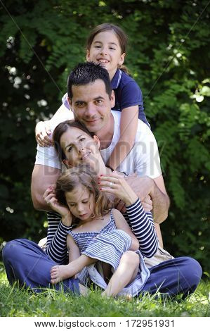 Happiness and harmony in family life. Happy family concept. Mother and father with their daughter in the park. Happy family resting together on the green grass. Family having fun outdoor