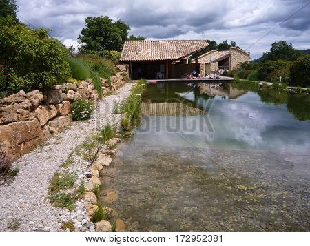Natural organic pool with gravel and shrub surround with covered barbecue area in the South of France