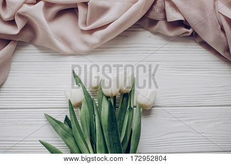 Hello Spring Flat Lay. Stylish White Tulips And Beige Soft Fabric On Rustic Wooden Table Background